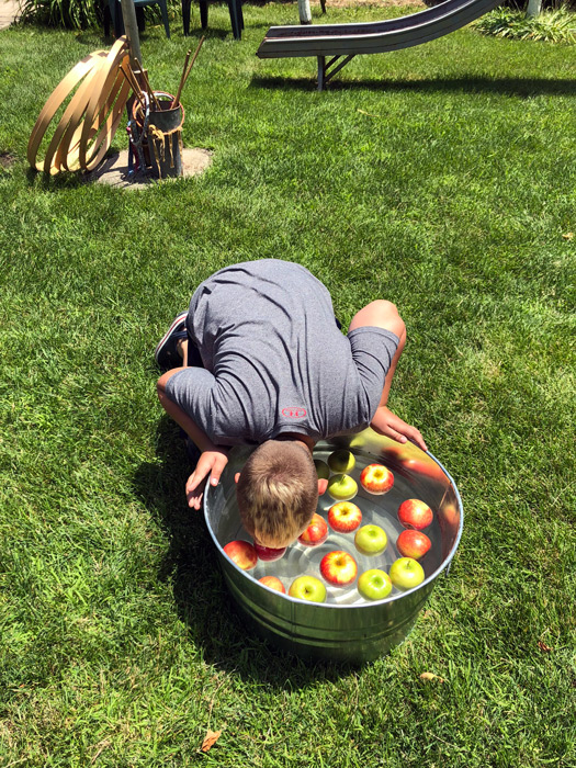 kid bobbing for apples